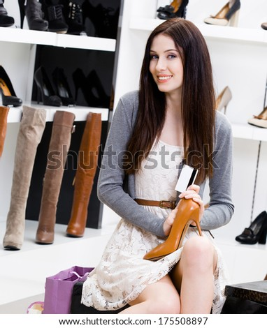 Woman keeps shoes and credit card in the footwear shop where she would like to buy new pumps - stock photo
