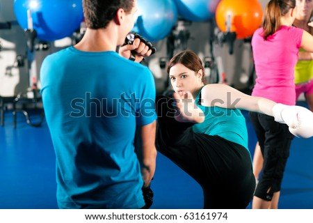 Woman Kick boxer kicking her trainer in a sparring session, in the background other boxers are hitting the sandbag - stock photo