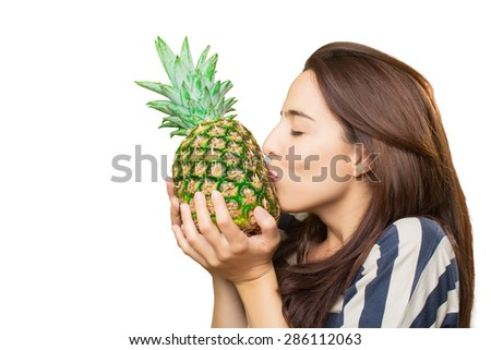 Woman kissing a pineapple. Over white background - stock photo