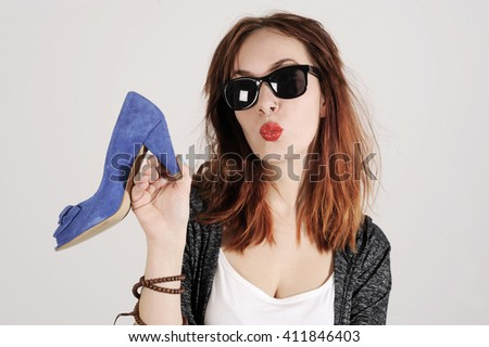 Woman kissing and holding a shoe. Women loves shoes concept. Fashion girl and blue high heels shoes. Beautiful young girl - stock photo