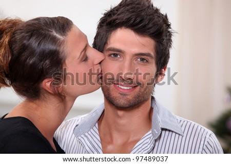 Woman kissing man on the cheek - stock photo