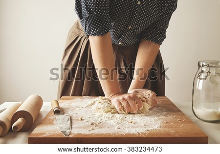 Woman kneads dough for pasta on wooden board near two rolling pins and jar with flour - stock photo