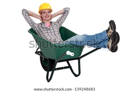 Woman laborer resting in a wheelbarrow - stock photo
