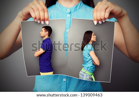 woman lacerating photo of young couple in quarrel over dark background - stock photo