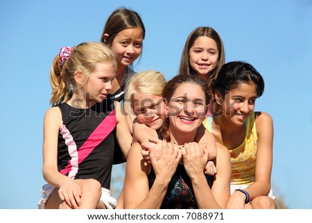 Woman laughing and five girls around her - stock photo