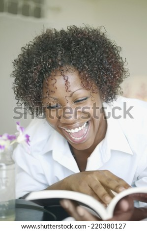 Woman laughing and reading book - stock photo