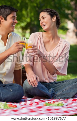 Woman laughing as she touches glasses of orange juice with her friend while they sit on a red and white picnic blanket - stock photo