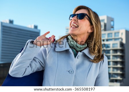 Woman laughing in town during her shopping - stock photo