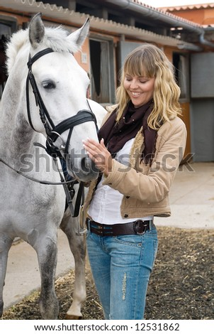Woman laughing with a white horse - stock photo