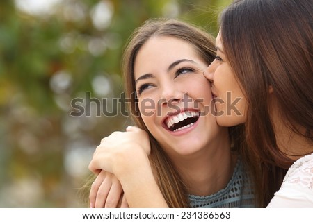 Woman laughing with perfect teeth while a friend is kissing her with a green background - stock photo