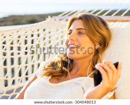woman laying and relaxing on a white hammock near a swimming pool, listening to music  - stock photo