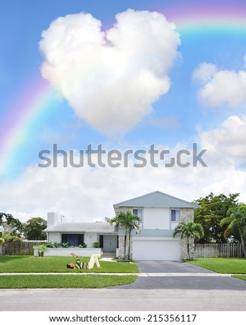 Woman laying on ground front yard of suburban home taking photo of  heart shape cloud in rainbow blue sky residential neighborhood USA - stock photo