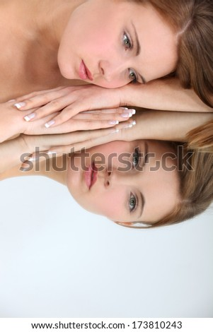 Woman laying on mirror - stock photo