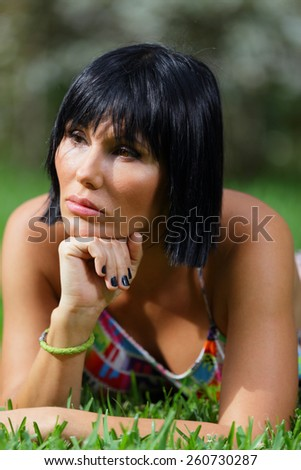 Woman laying on the grass with hand under chin - stock photo