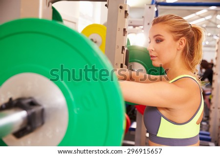 Woman leaning on a barbells at a squat rack in a gym - stock photo