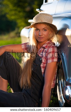 Woman leaning on a classic car - stock photo