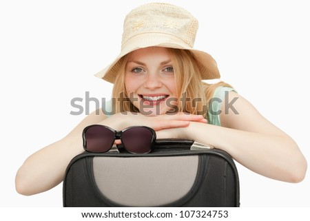 woman leaning on a suitcase while smiling against white background - stock photo