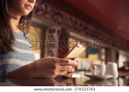Woman leaning on the bar counter and text messaging with her mobile, hands close up - stock photo