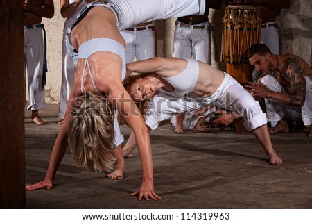 Woman leans in to dodge her attackers foot in Capoeira - stock photo