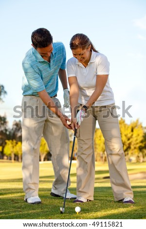 Woman learning how to play golf outdoors - stock photo