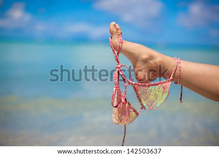 Woman leg holds pink bra isolated on exotic background - stock photo