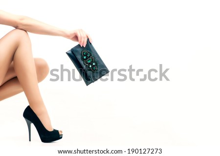 Woman leg in high heels and hand bag isolated on white - stock photo