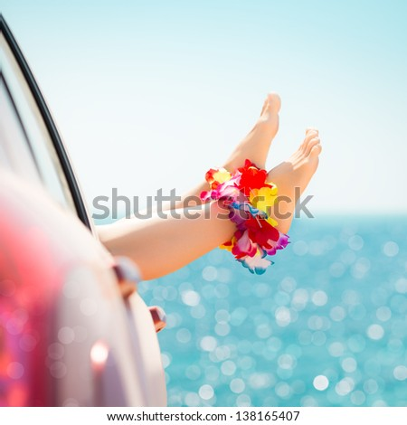 Woman legs against emerald sea background. Summer vacations concept - stock photo