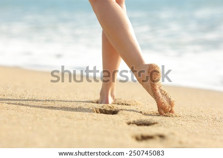 Woman legs and feet walking on the sand of the beach with the sea water in the background - stock photo