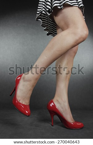 Woman legs and feet wearing dress  shoes over grey background - stock photo