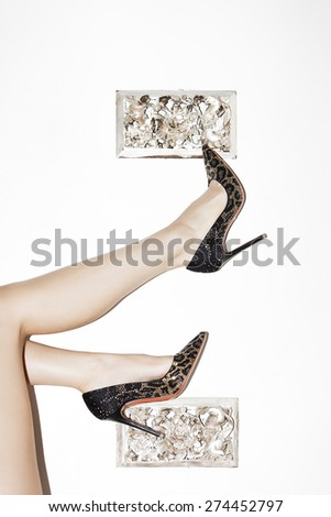 Woman legs and feet wearing spotted high heels shoes - stock photo