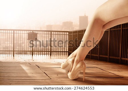 woman legs and wooden terrace with landscape of city and sunset  - stock photo