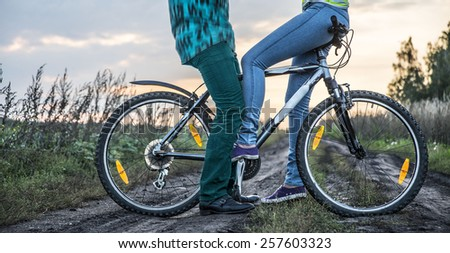 woman legs carried by bicycle his boyfriends on a bike at sunset sky with clouds background Cute young adult couple opposite each other on summer spring land in green grass field - stock photo