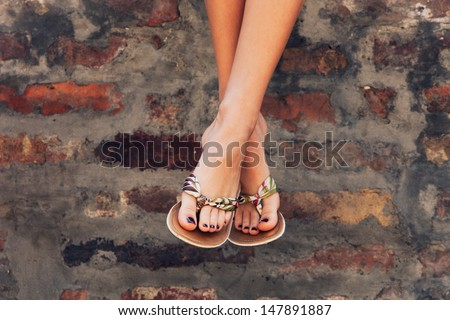 woman legs in  summer flat slippers outdoor day  shot  in city - stock photo