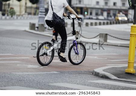 woman legs on a urban bike on the road - stock photo