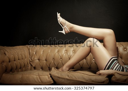 Woman Legs On The Sofa - stock photo