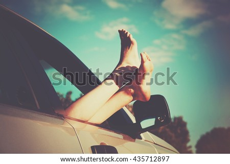 Woman legs out car window. Freedom or traveling concept - stock photo