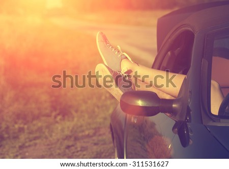 Woman legs out of car windows - stock photo