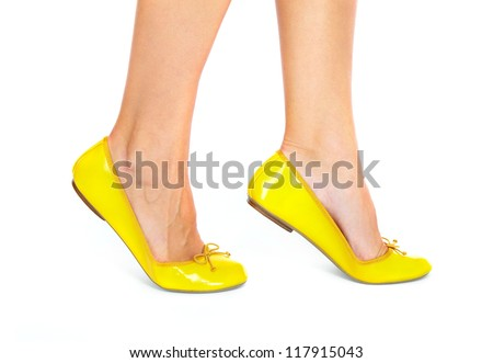 Woman legs with a yellow shoes.  Isolated on white background. - stock photo