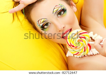 woman licks candy with beautiful make-up - stock photo