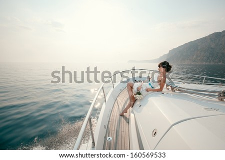 woman lies on a luxury yacht in the sea and looking to the horizon - stock photo