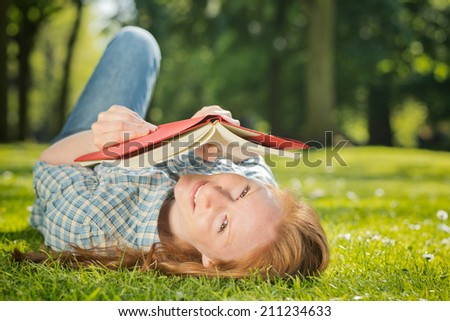 Woman lies on her back in a park while reading a book. - stock photo
