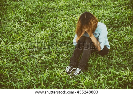 Woman life concept: sad woman hug her knee and cry in meadows. - stock photo
