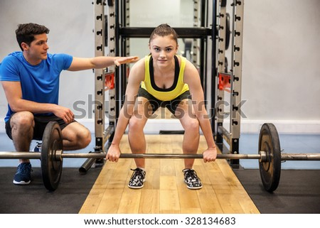 Woman lifting barbell and weights with trainer watching at the gym - stock photo
