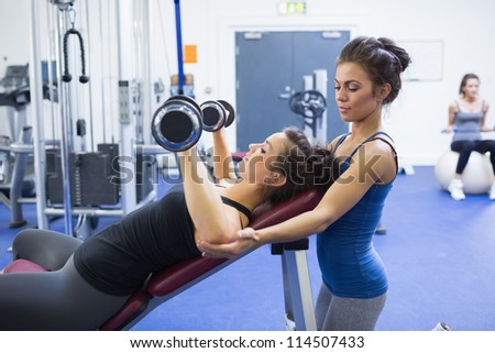 Woman lifting weights and her female trainer - stock photo
