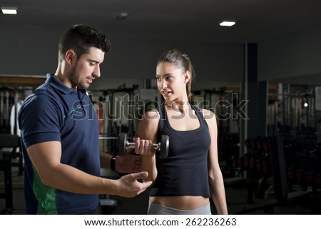Woman lifting weights at gym training biceps. Personal trainer helps. Focus is in woman.Low key image. - stock photo