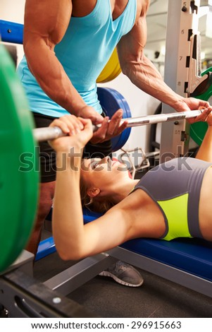 Woman lifting weights with the help of trainer, side view - stock photo