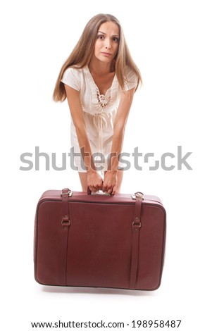 woman lifts a heavy suitcase, isolated on white background - stock photo