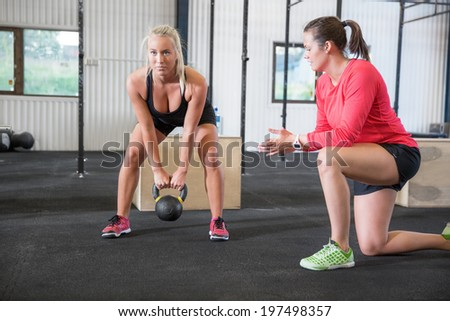 Woman lifts kettlebell with personal trainer - stock photo
