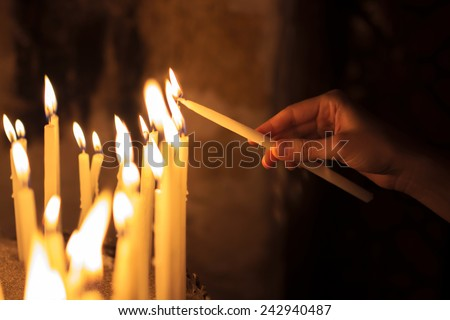 woman lighting candles  in a church - stock photo