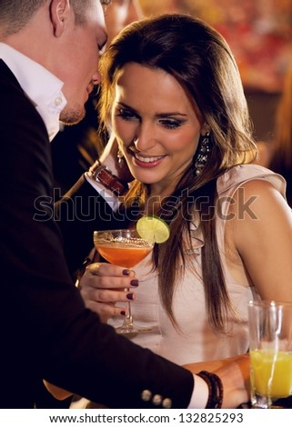 Woman listening as her boyfriend whispers something romantic to her - stock photo